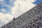 Amateur Mountaineering Against The Blue Sky With Clouds. Man Climbing Up Hill To Reach The Peak Of T poster
