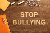 Office stationery and text STOP BULLYING on wooden background, top view poster