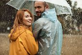 Happy Couple Walking Under Umbrella Hiding From Rain. They Are Turning In Delight Enjoying Leisure T poster