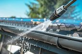 Spring Rain Gutters Cleaning Using Pressure Washer. Closeup Photo. poster