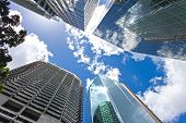 View Looking Up At Blue Cloudy Sky Through Skyscrapers Reflecting Clouds And Other Buildings In Cbd  poster