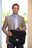 Businessman coming through a domestic doorway poster