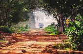 Driving A Truck Through A Dirt Road Of A Farm. Truck On A Dirt Road Surrounded By Trees. poster