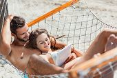 Smiling Couple Using Digital Tablet While Relaxing On Hammock On Beach poster