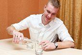 Drunken young man pouring vodka