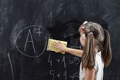 Schoolgirl Wiping Blackboard With A Sponge After Solving Math Problems And Getting An A In Math. Foc poster