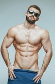 Bodybuilder Posing. Beautiful Sporty Guy Male Power. Fitness Muscled In Blue Shorts And Sunglasses.  poster