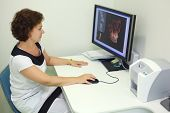 Dentist carefully looks skull X-rays at computer monitor in dental clinic.