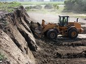 stock photo of heavy equipment operator  - heavy equipment operator mining dirt from a hill - JPG