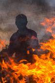 picture of siluet  - Dark siluete of man behind orange fire - JPG