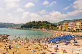 crowded beach on the Ligurian Sea, Lerici , Italy with blue umbrellas