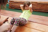 Little girl makes abdominal crunches for limited time on wooden platform