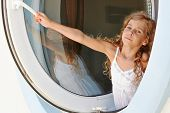 Little girl in white dress opens window made as porthole