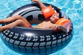 Happy boy lies with eyes closed on wheel shaped inflatable mattress in pool