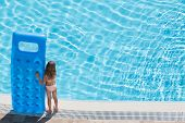 A girl stands on the edge of the pool with inflatable mattress