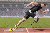 stock photo of sprinters  - Explosive start of an athlete with handicap - JPG