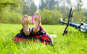 Barefoot Cyclist On A Halt Reads Lying In Fresh Green Grass