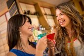 Two women having drinks at the bar looking very happy