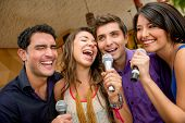 stock photo of singer  - Group of friends having fun karaoke singing at the bar - JPG