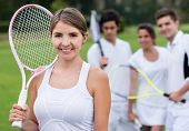 Female tennis player holding racket with her team at the background