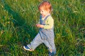 Smile Child In The  Jeans Coverall Walk On The Grass
