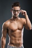 Shirtless male model posing with glasses over a blue background