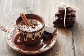stock photo of stick  - Cup of hot chocolate cocoa with cinnamon sticks on vintage wooden background - JPG
