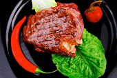 meat savory : beef grilled and garnished with green lettuce and red chili hot pepper on black dish i