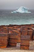Combustible oxidado y tambores químicos en la costa ártica con iceberg en fondo