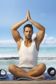 Athletic young man practicing yoga on the beach, meditating in prayer position eyes closed.