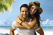 Attractive young loving couple enjoying summer holiday on the beach piggyback,