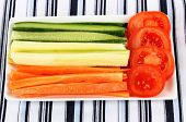 Assorted raw vegetables sticks in plate on table close up
