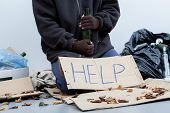 stock photo of homeless  - Homeless alcoholic sitting around the trash bags and holding an empty bottle - JPG