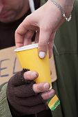 stock photo of beggar  - Hot drink for a homeless beggar closeup - JPG