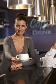 Portrait of attractive female bartender handing coffee cup towards camera.