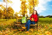 picture of 11 year old  - Autumn portrait of a 11 years old girl sitting on the bench in the park after school with backpack - JPG
