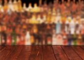 stock photo of condensation  - Dark wooden table against interior of bar with alcohol bottles - JPG