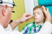 Medical otolaryngologist ear nose throat doctor rinsing nose at boy child