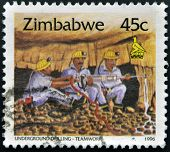 ZIMBABWE - CIRCA 1995: A stamp printed in Zimbabwe shows Underground drilling teamwork circa 1995