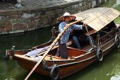 A Boatwoman Transports Tuorists In Her Traditional Wooden Boat In Ancient Tongli Watertown,  Jiangsu