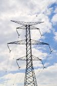 stock photo of hydro-electric  - Large electrical tower with bent insulators on cloudy sky - JPG