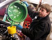 Automotive Technician Auto Mechanic Refills Radiator After Service