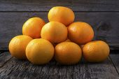Mandarin Oranges In Pile On Rustic Wood