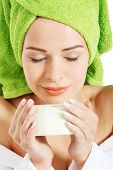 image of turban  - Beautiful woman in bathrobe and turban smelling body lotion - JPG