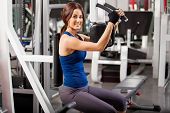 Happy brunette working out in a gym