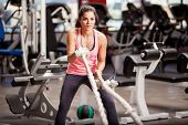 stock photo of rope pulling  - Pretty Hispanic young woman doing some crossfit exercises with a rope at a gym - JPG