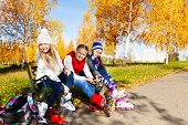 Three Girls Putting On Roller Blades In The Park