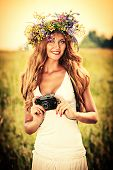 Portrait of a romantic smiling young woman in a circlet of flowers standing with her old camera outd