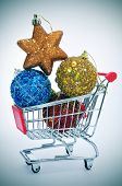 a pile of christmas ornaments in a shopping cart, depicting the christmas shopping concept