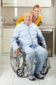 Demented senior man in wheelchair with extended care assistant